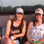 women in baseball caps at baseball stadium