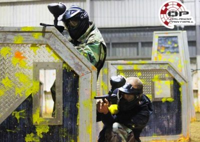 Two Friends Playing Paintball Indoors
