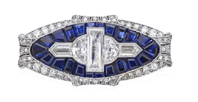 An Art Deco sapphire and diamond brooch, 1930s Of oval form, set to the centre with a geometric formation of baguette, half-moon shaped and bullet-shaped diamonds, all within a surround of calibré-cut sapphires and a pierced millegrain-set border of old round brilliant and single-cut diamonds with scroll detail, length 38mm, the diamonds estimated to weigh approximately 3.10cts in total