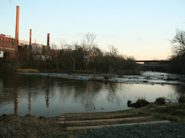 wooden steps lead to the river with a view across it to the Granite Mill on the left and bridges on the right with trees along the riverbanks