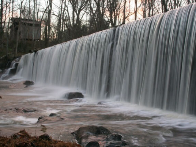 a photo of the river pouring over the dam at Altamahaw in the winter with an old farm structure in the background