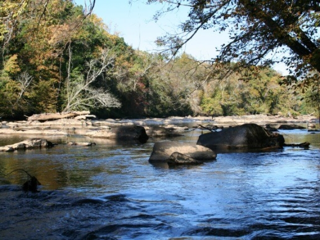 a photo of the Haw River in the Fall in the Glencoe section with rocks in the river