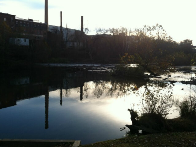 a photo of the Haw River at sunset looking from Red Slide Park across at Granite Mill