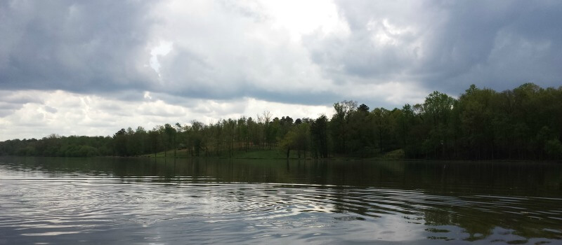photo of rippling water on Saxapahaw lake with light and dark stormcloud sky and riverbank with trees in background