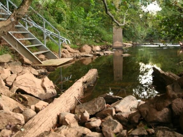 a photo looking downriver with the steps at Shallow Ford Natural Area put in on the left and rocks in the foreground with trees in the background