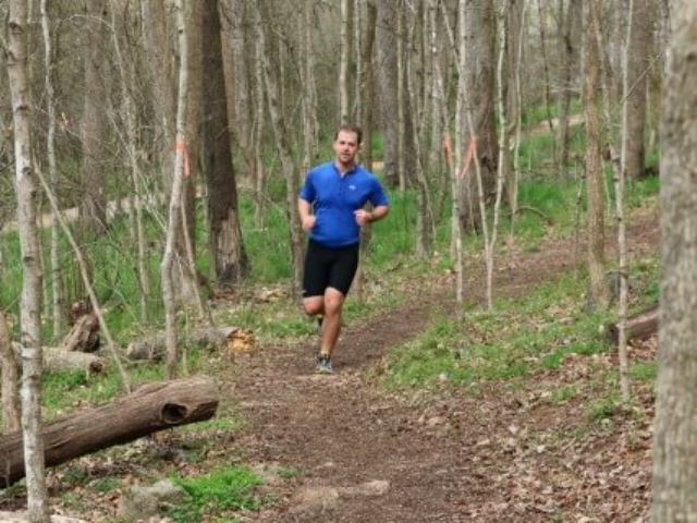 photo of a man in a blue shirt and black shorts running on the HRT in Saxapahaw