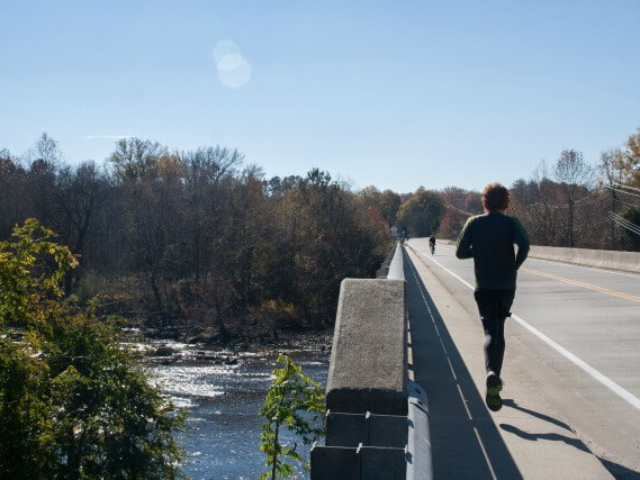 photo of a runner and cyclist on a bridge with the river and trees to the left
