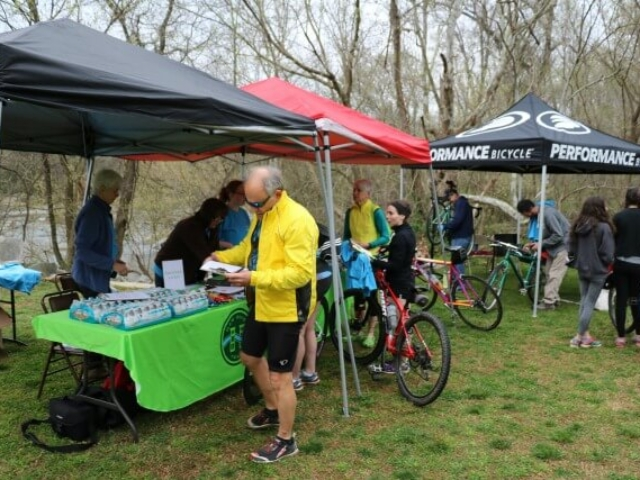 a registration table under two popup tents and a Performance Bicycle tent with staff working the registration table and participants with their bikes checking in