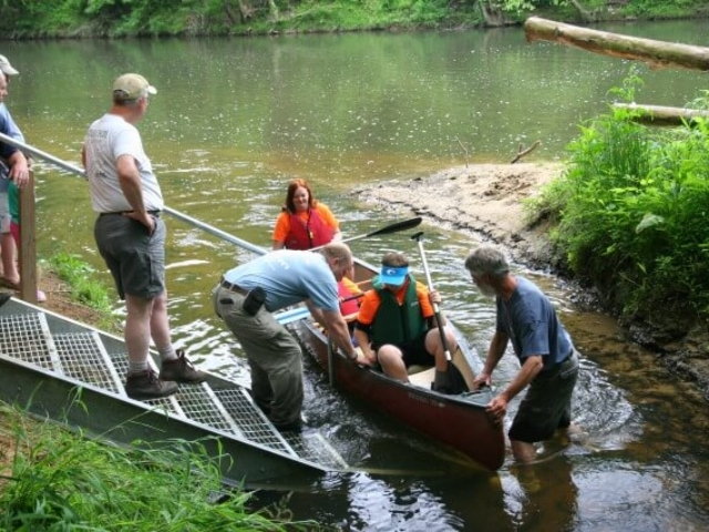 a canoe with a family pulled up to the steps in the river with several people assisting them with getting out of the canoe