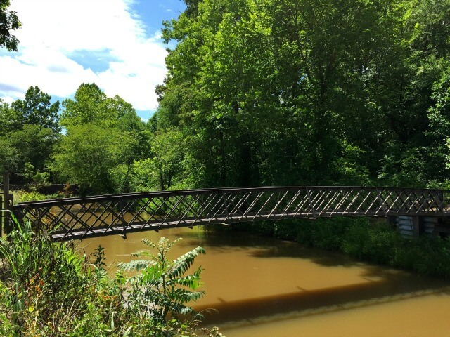 a photo of a metal pedestrian footbridge crossing the river at Altamahaw with trees in the background