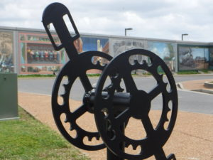 A bike rack shaped like a pedal and gears is the foreground of a floodwall mural