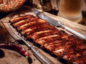 Delicious BBQ ribs with coleslaw and beer on wooden table
