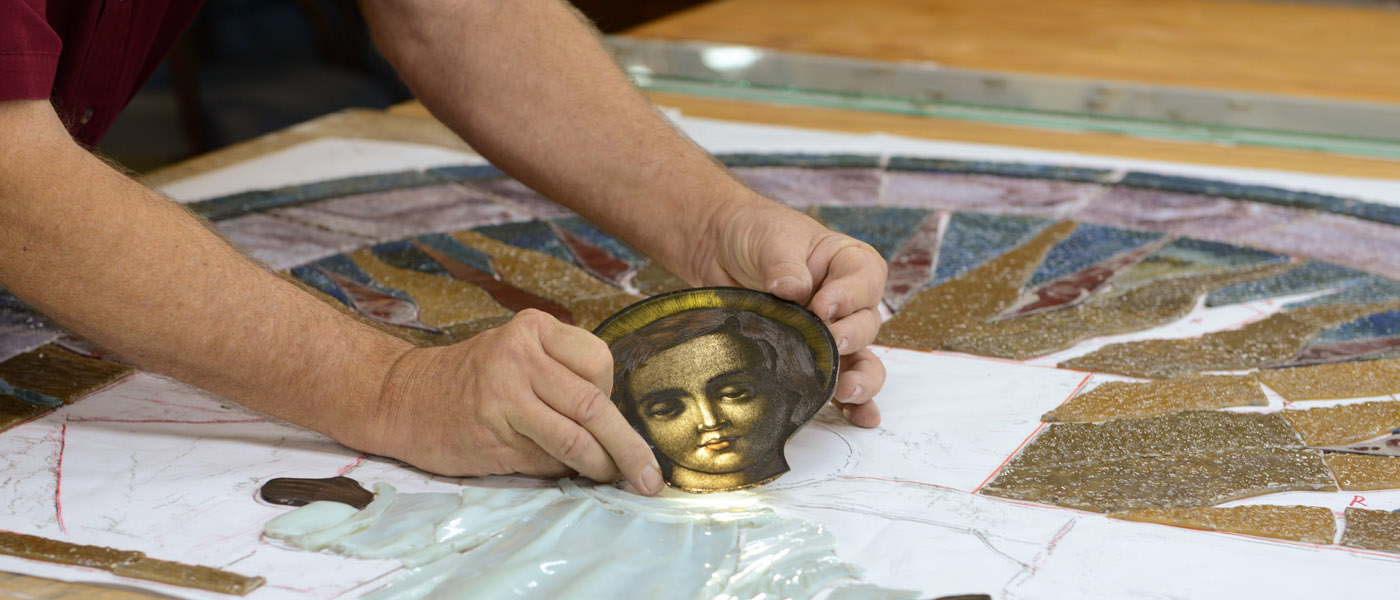A close-up of a painted face in a stained glass restoration project in progress