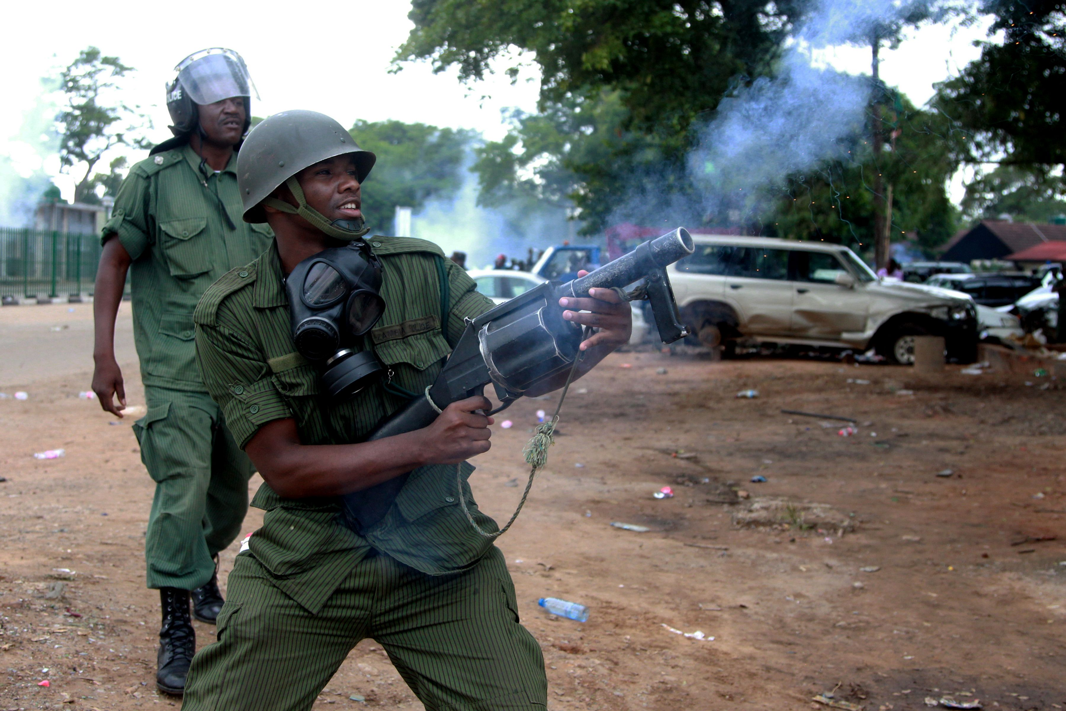 A Zambian police officer fires tear gas to supporters of the opposition United Party for National Development (UPND) outside the Woodlands Police Station in Lusaka on March 2, 2016. The supporters turned to show solidarity to their party vice-president Geofrey Mwamba who has since been arrested and charged with unlawful drilling. / AFP / Dawood SALIM        (Photo credit should read DAWOOD SALIM/AFP/Getty Images)