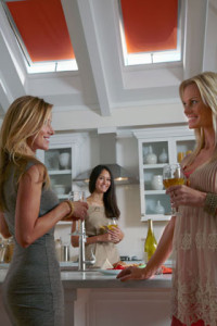Three ladies in a kitchen with skylights beaming light on them.