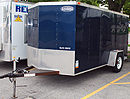 Left side of the blue 6' x 12' enclosed utility trailer for rent