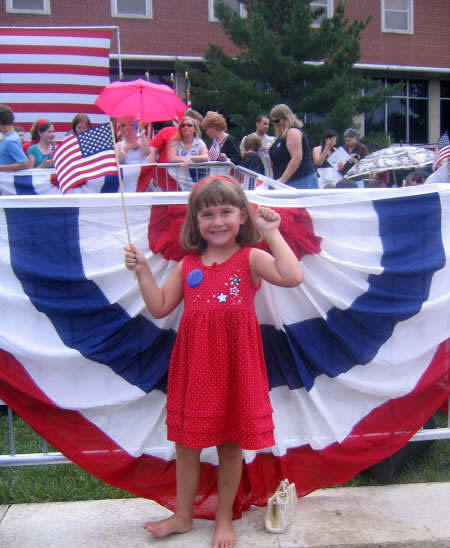 Young child holding a flag of the United States of America with one of our Bunting flags in the background.