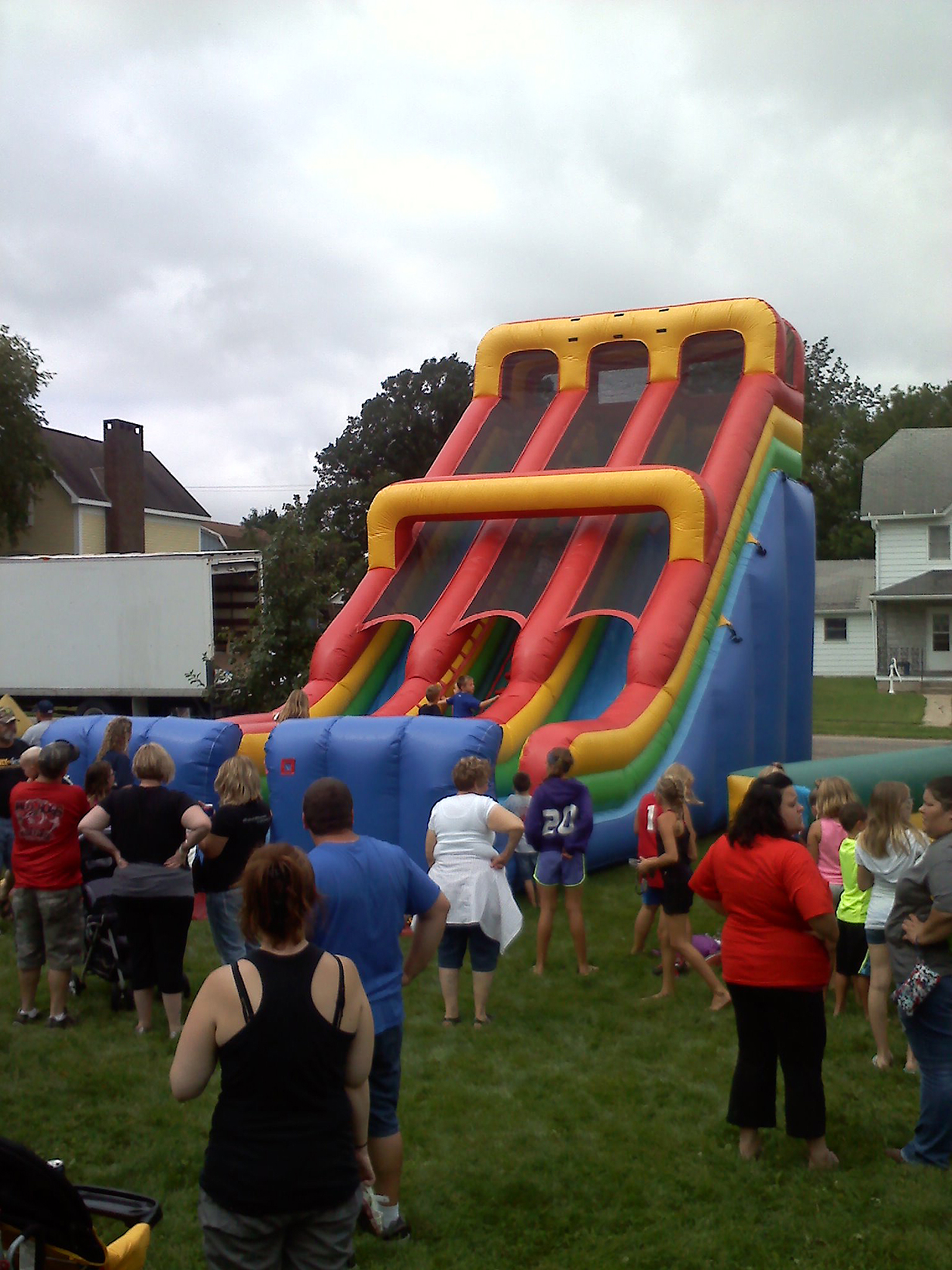 Crowd watching kids play on inflatable slide