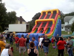 Large crowd of people watching the kids play on the inflatable slide