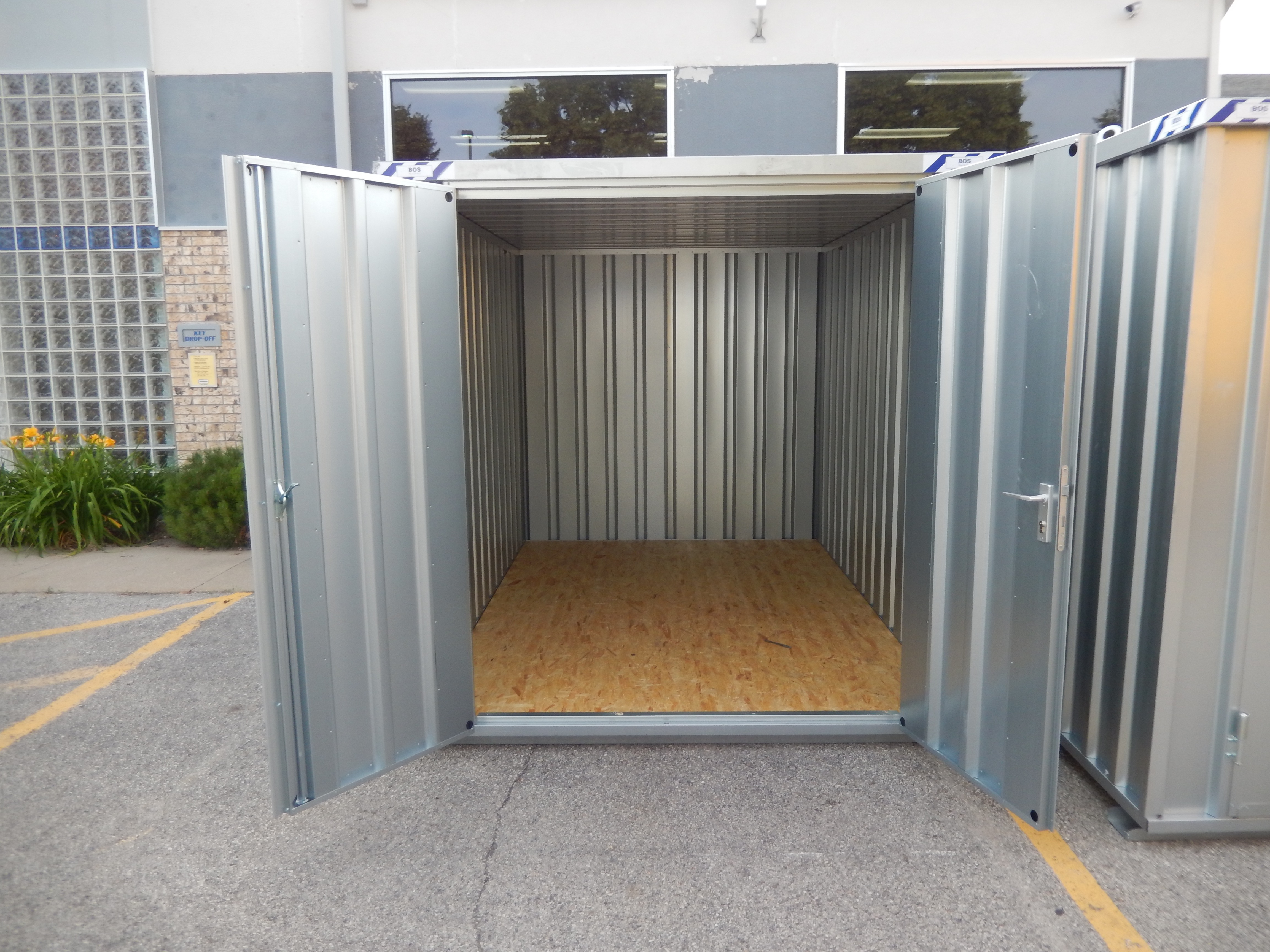 Open door to small portable temporary steel storage shed