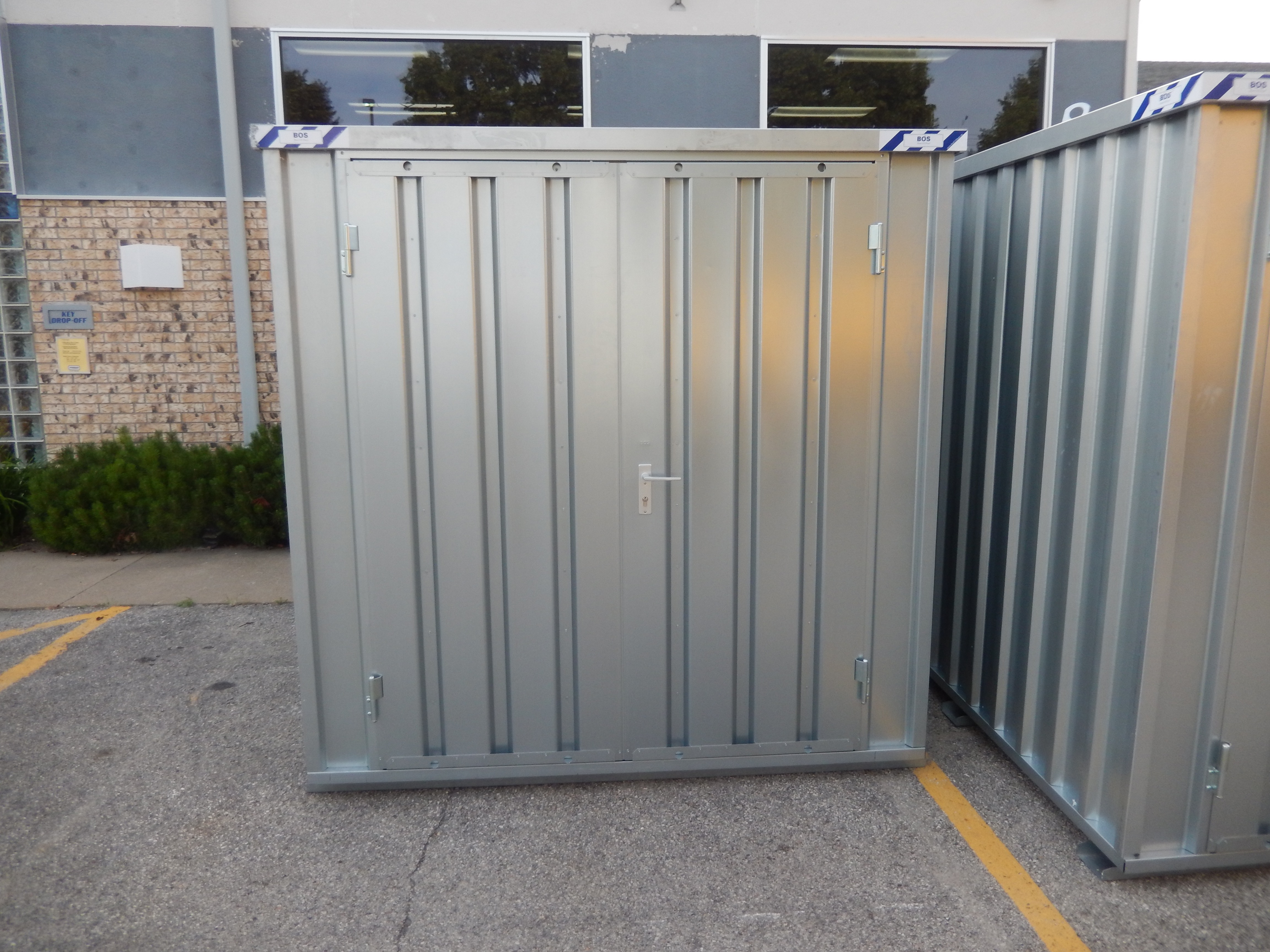 Small portable temporary steel storage shed with door closed