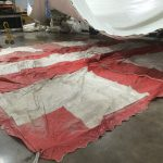 Used 20' x 30' red & white: Rope and Pole tent for sale on the ground.