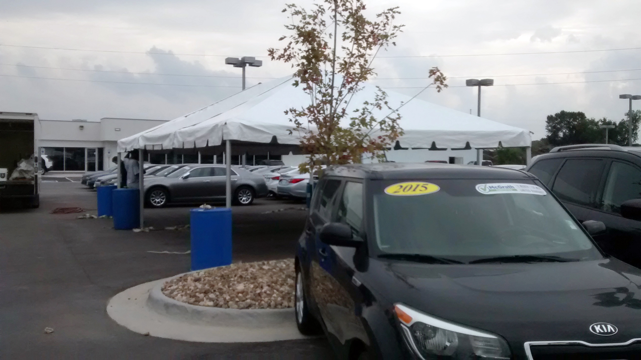 20′ x 30′ frame tent for the grand re-opening at Coralville Used Car Superstore with water barrels