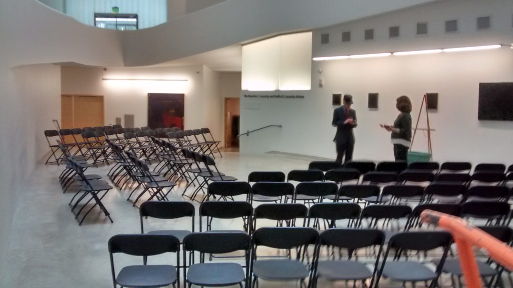 Black chairs set up in rows for a conference