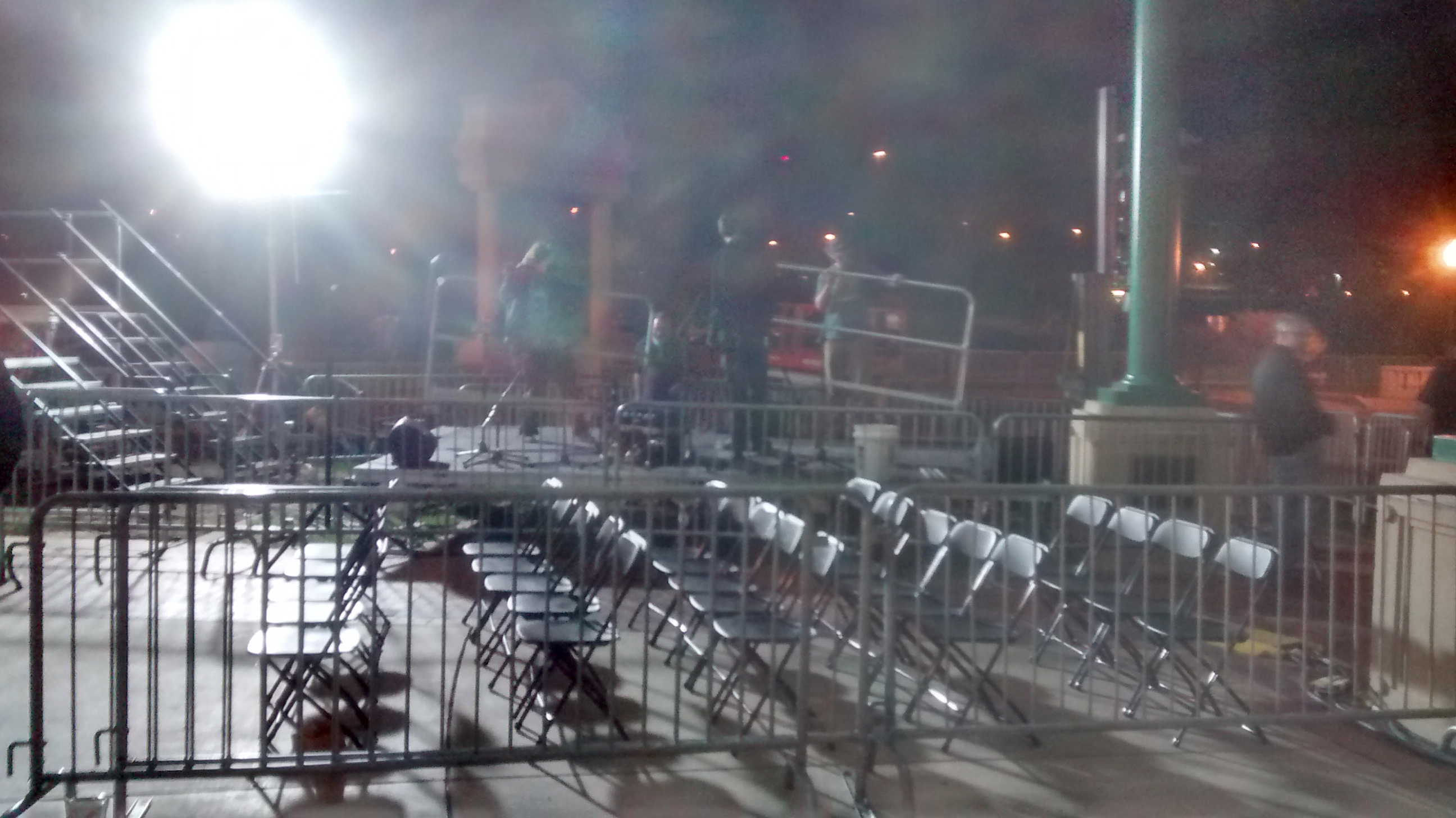 Barricade and seating area with band stage in the background setup for political event at Larsen Park Road, Sioux City, Iowa