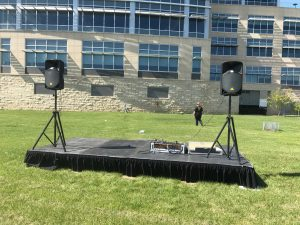 8' x 16' stage with PA Pro Package and tripod stands behind UICCU Financial Center Building in Iowa