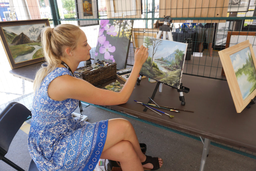 Emily Gustafson painting Emerging Artists under our tent at the Summer of the Arts festival in June 2017