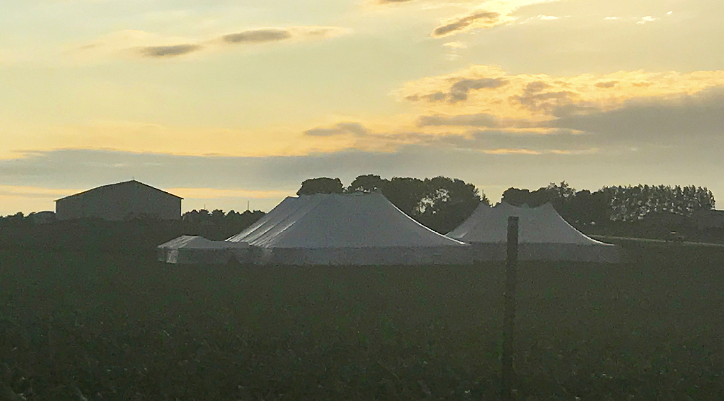 Event with 20' x 60' frame tent with a glass door on the left with 80' x 150' rope and pole and 60' x 90' rope and pole tent on the right with two 10' x 10' frame tents connecting them all together