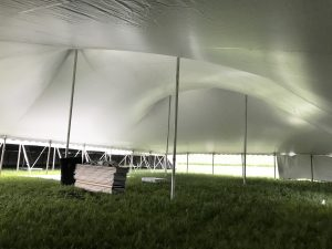 """Under a 60' x 90' """"Twin Pole"""" rope and pole tent"""