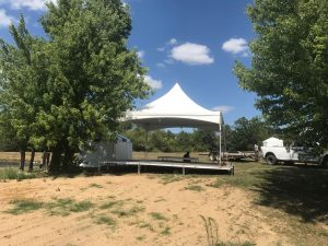 20' x 20' Tentnology frane tent on top of stage for an Outdoor corporate event setup for West Liberty foods in Libertyville, Iowa