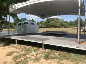Stage with tent set up on top of it for Outdoor corporate event setup for West Liberty foods in Libertyville, Iowa