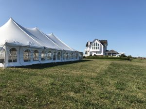 Side of 40' x 80' rope and pole wedding tent setup in Fairfield, Iowa with home