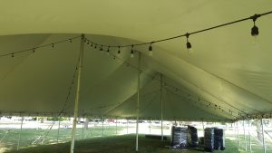 Under a 40' x 80' rope and pole tent at a campground near Muscatine, Iowa