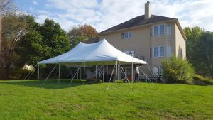 20' x 30' rope and pole tent with a home in the background