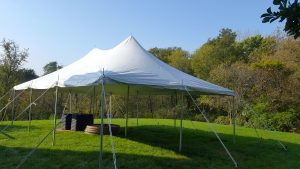 Backyard with a white 20' x 30' rope and pole tent