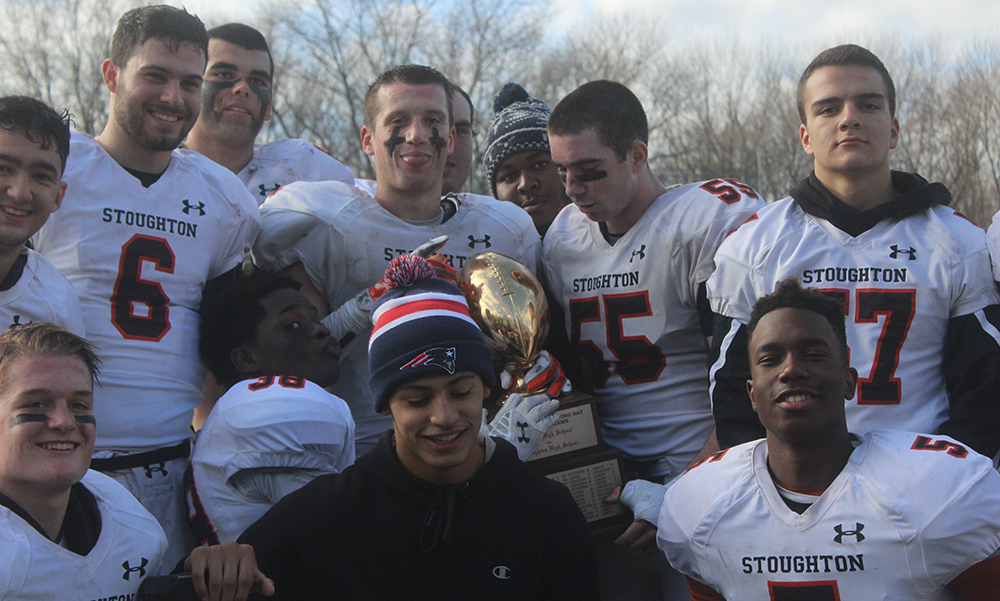 Stoughton seniors celebrate with the trophy after their 26-13 win over Canton. (Ryan Lanigan/HockomockSports.com)