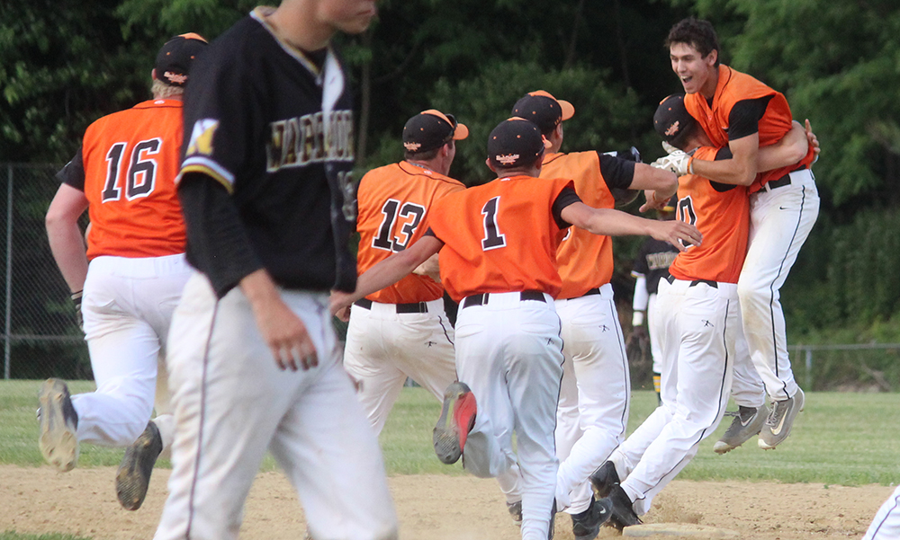 Stoughton players rush to celebrate with Pat Hagerty (far right) after driving the winning run in. (Ryan Lanigan/HockomockSports.com)