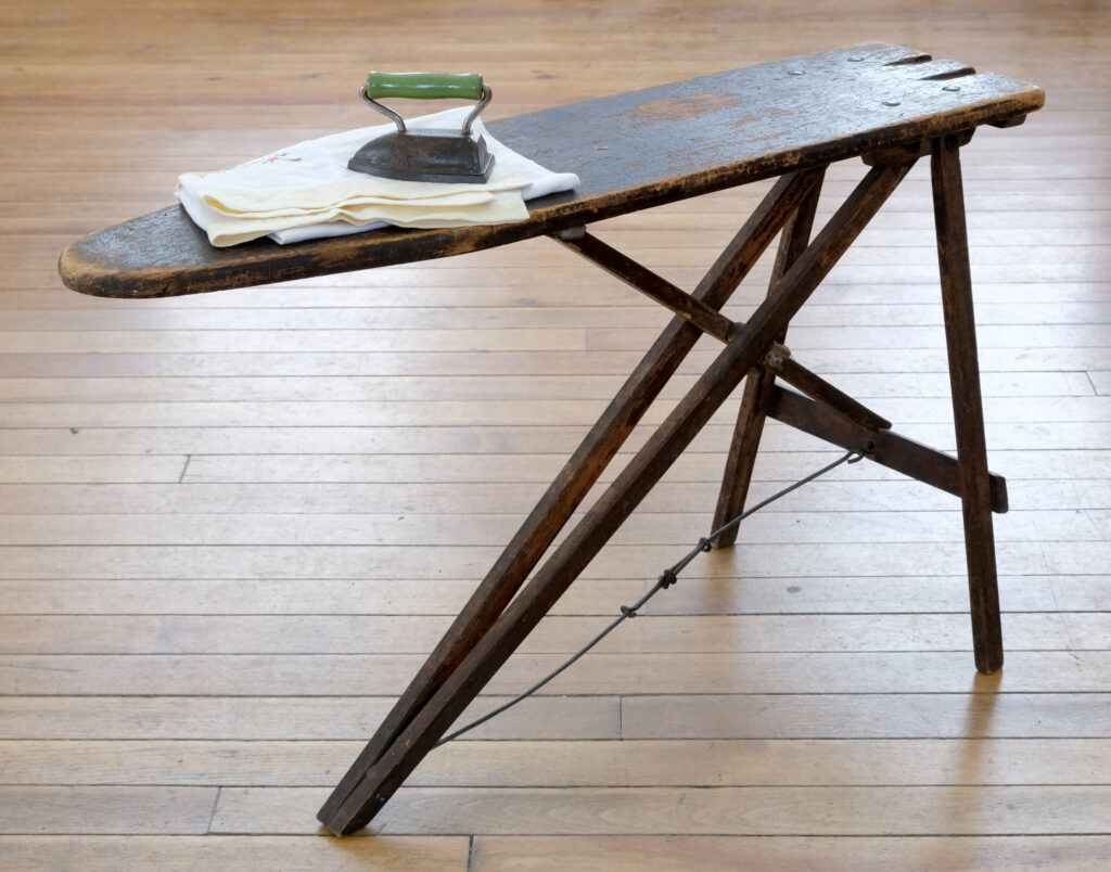 The Museum's child's ironing board with a mini iron and cloth on top