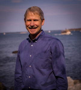 Photo of Pastor Ric in front of a boat on the water