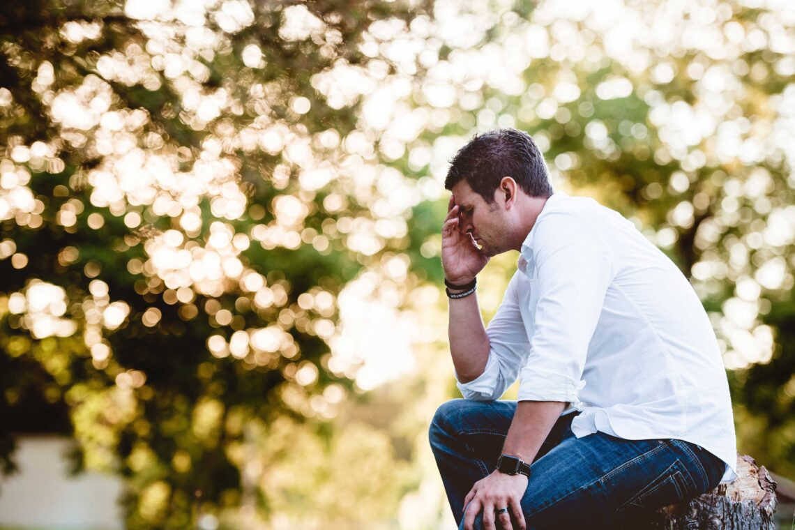 photo of man praying with concern outdoors