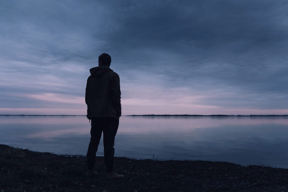photo of man standing alone on shore