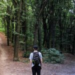 Photo of man in woods before two separate paths