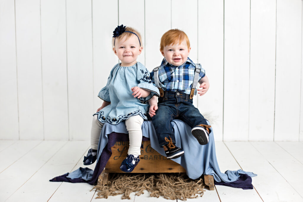 Twin boy and girl babies sitter session with matching blue outfits.