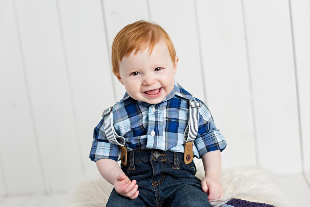 Baby boy sitter session with suspenders and blue plaid shirt on white wood background.