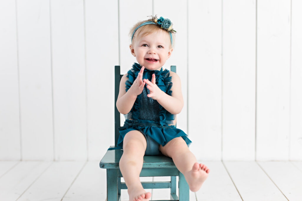 Baby girl sitter session with teal romper and garden tieback sitting on a teal chair with a white wood background.