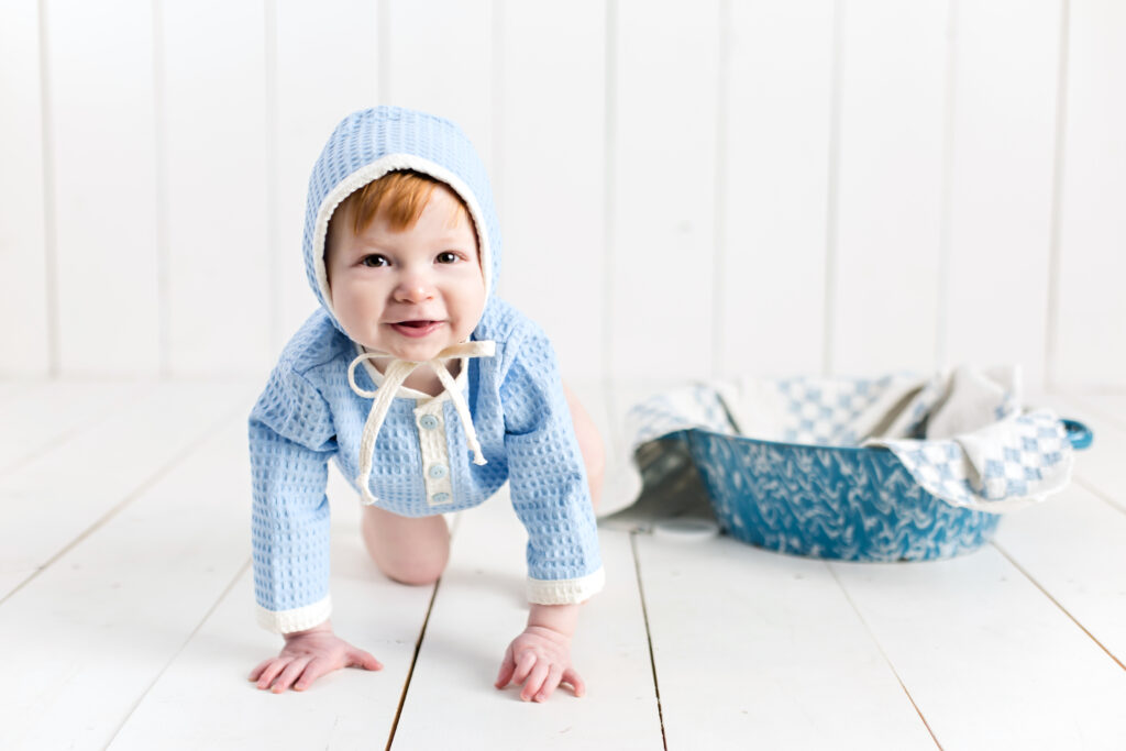 Baby boy sitter session with light blue romper and bonnet sitting in a bowl with a quilt piece.